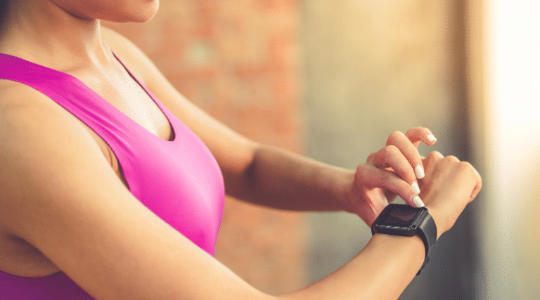 Woman in pink sports bra wearing a Fitbit