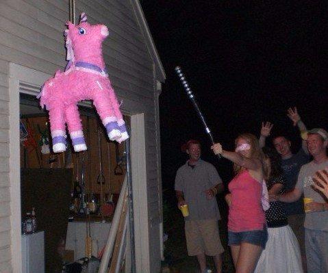 Woman hitting a pink pinata