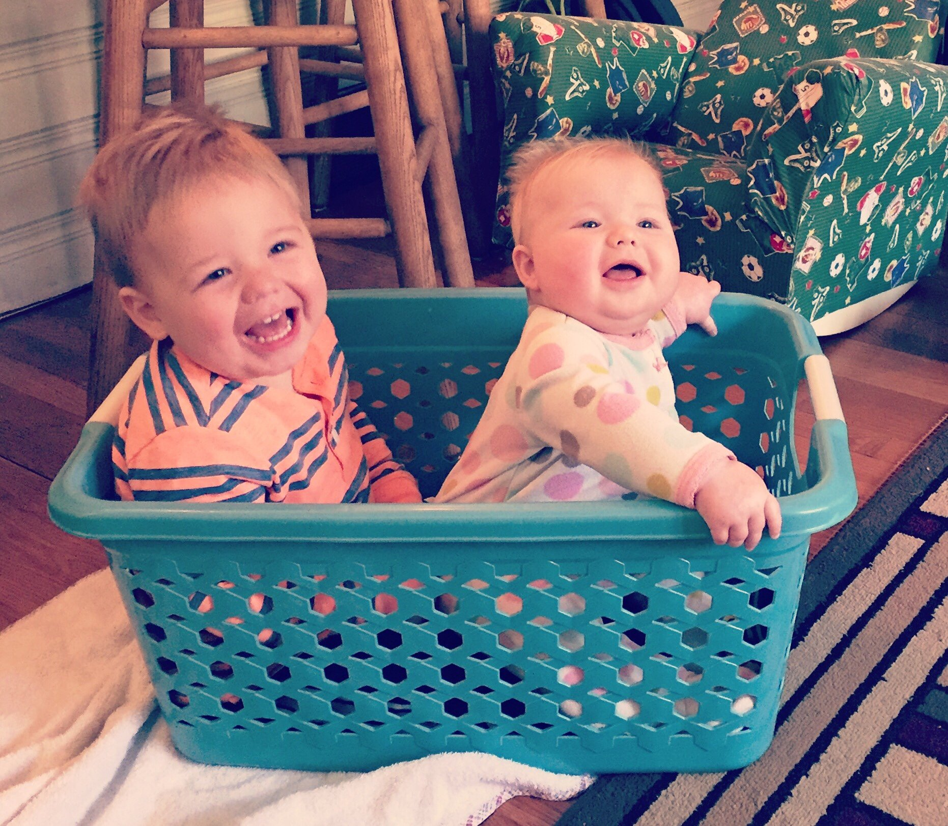2 under 2. Toddler and baby in a laundry basket.