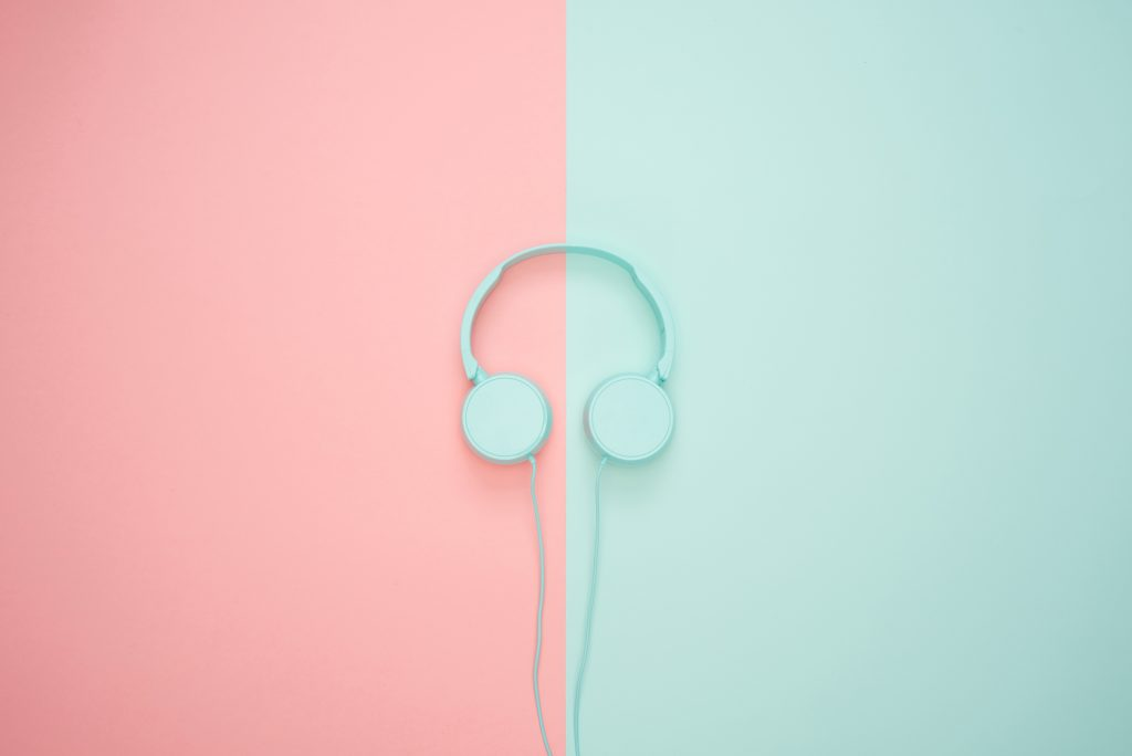 Storytelling Podcasts recommendations. Image: of headphones on blue and pink background. Image cred: https://photos.icons8.com/