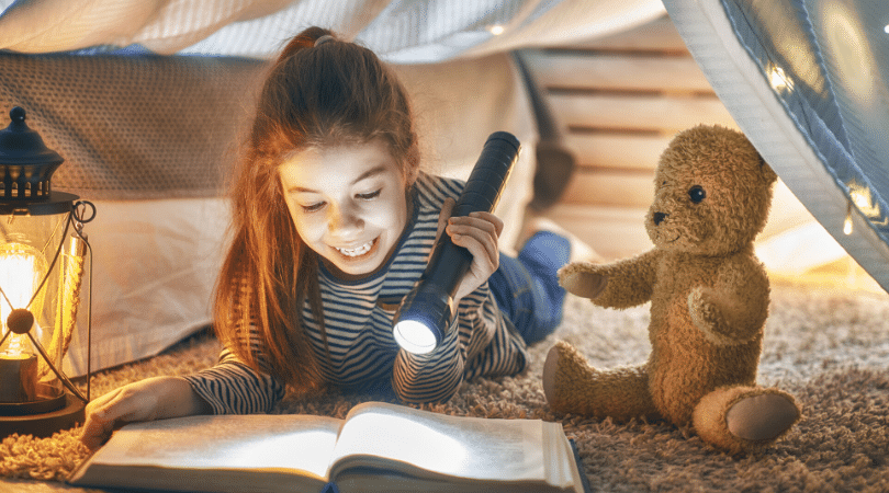 Child reading a book with a flashlight