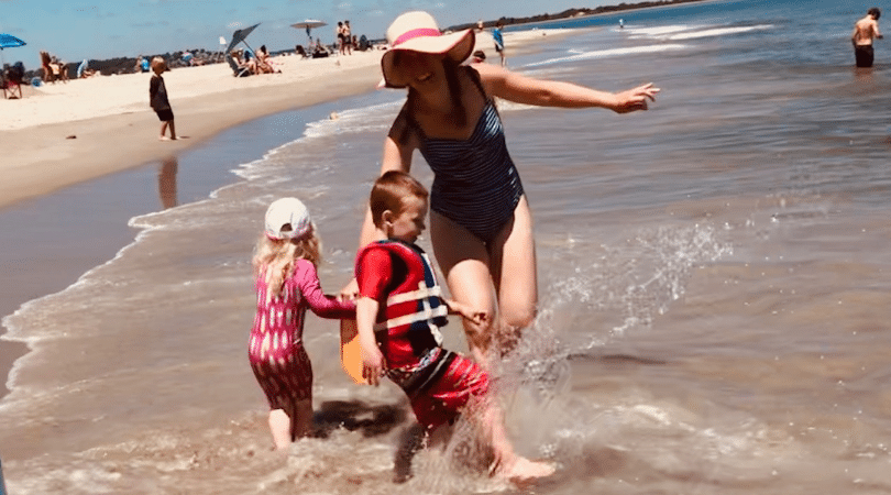 Mother at beach with two small children playing in the water