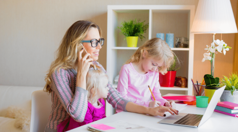 Mom on the phone at the computer with two young girls. Websites moms returning to work need to know.