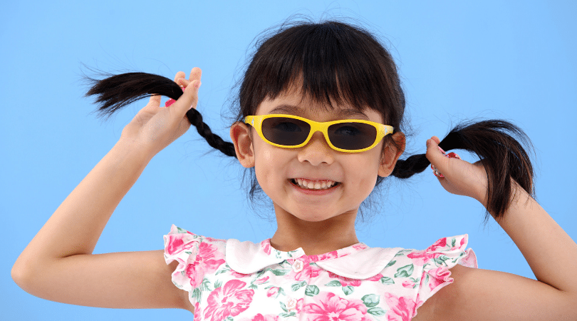 Young girl with sunglasses and braids smiling