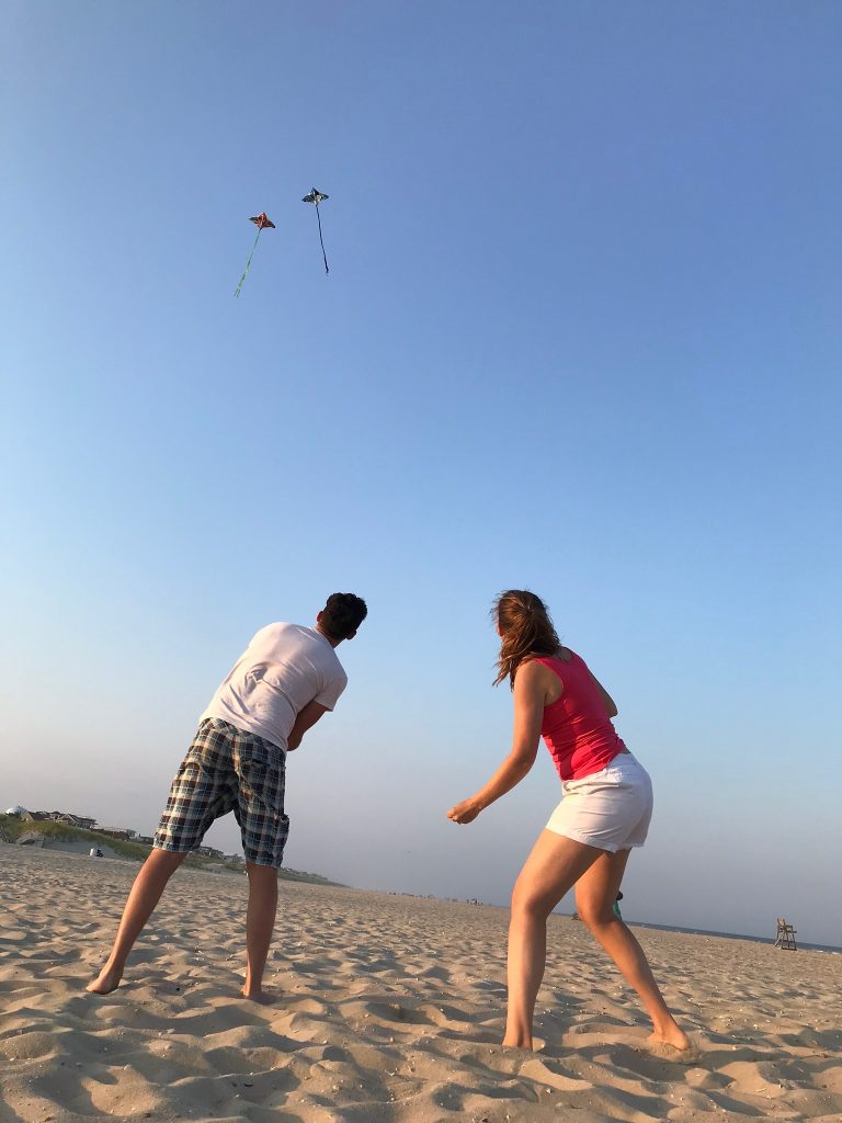 Man and woman flying kites on the beach