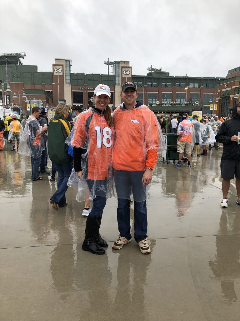 Couple in front of Lambeau Field in Denver Broncos gear. 48 hours in Wisconsin