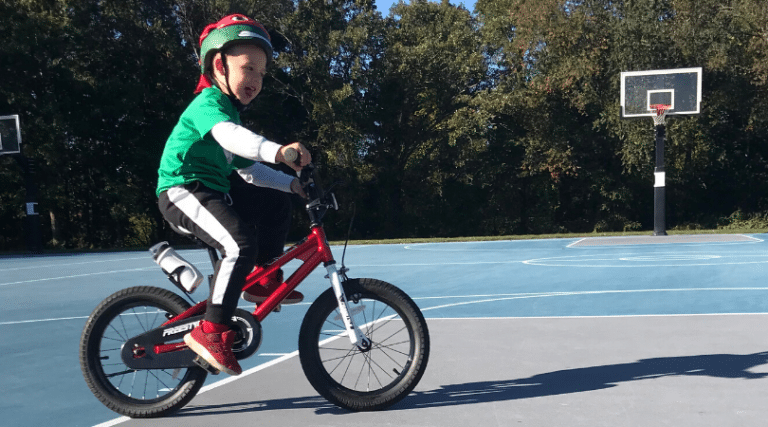 4-year-old boy in green shirt riding a red bike