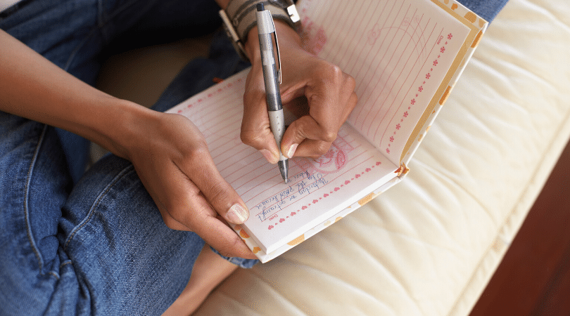 Woman writing a one line a day journal