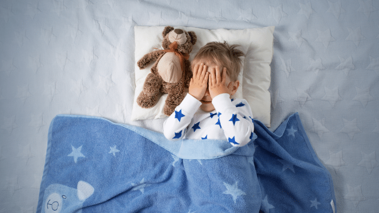 Child in blue blanket covering his eyes