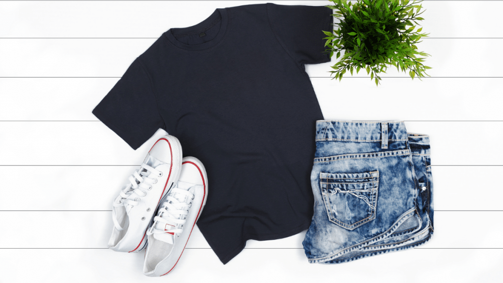 Blank tshirt flatlay with white sneakers, plant, and jean shorts