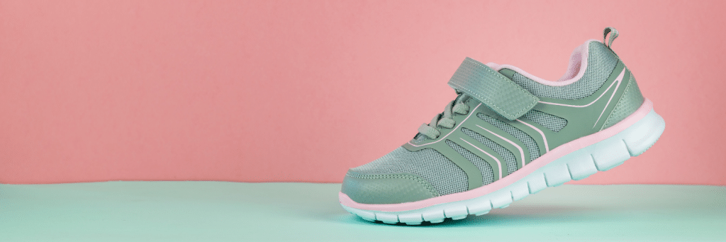 green sneaker on light green floor with pink wall