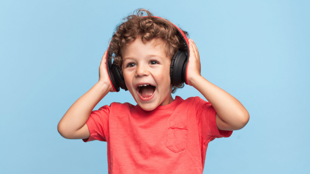 child smiling in red shirt with headphones