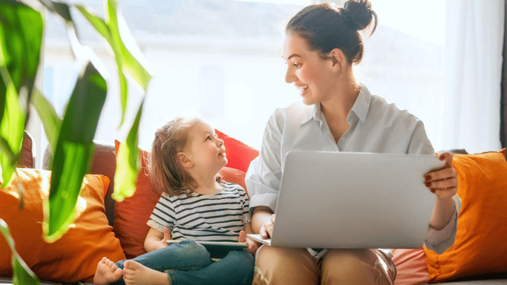 woman at computer with child on couch
